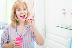 Woman brushing teeth in bathroom Royalty Free Stock Photography