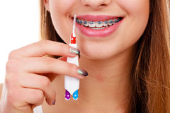 Woman brushing teeth with braces using brush. Dentist and orthodontist concept. Young woman cleaning and brushing teeth with blue braces using toothbrush Royalty Free Stock Images