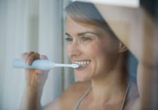 Woman brushing teeth with electric toothbrush Stock Photography