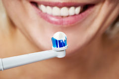 Woman brushing teeth electric toothbrush with toothpaste. Closeup Stock Photos