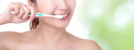 Woman brushing teeth with green background Stock Image