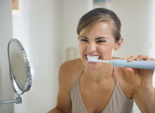 Woman brushing teeth with grimace on face. Young woman brushing teeth with grimace on face royalty free stock photography
