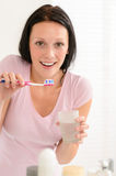 Woman brushing teeth holding glass of water Stock Photography
