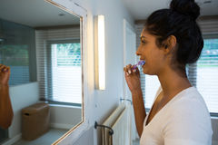 Woman brushing teeth at home stock image