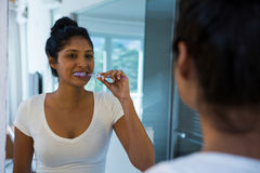 Woman brushing teeth with reflection on mirror. In bathroom at home royalty free stock photography