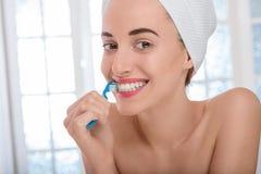 Woman brushing teeth Stock Images