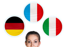 Woman and bubbles with countries flags. Young woman surrounded by dialogue bubbles with countries flags. Germany,  Italian, Czech. Learning of foreign languages Royalty Free Stock Images