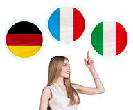 Woman and bubbles with countries flags. Young woman surrounded by dialogue bubbles with countries flags. Germany,  Italian, Czech. Learning of foreign languages Royalty Free Stock Photo