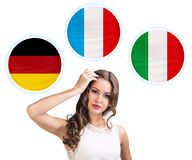 Woman and bubbles with countries flags. Young woman surrounded by dialogue bubbles with countries flags. Germany,  Italian, Czech. Learning of foreign languages Stock Image