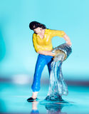 Woman with Bucket. A figurine of a woman pouring a bucket of water Royalty Free Stock Photos