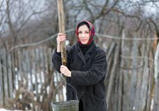 Woman with  bucket collecting water from  well Stock Image