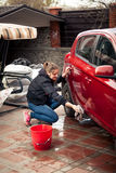 Woman with bucket and rag washing red car Royalty Free Stock Photography
