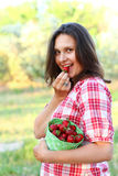 Woman with a bucket of strawberries, eating strawberries Royalty Free Stock Photography