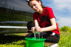 Woman with Bucket Wringing Out Sponge Next to Car Stock Photo