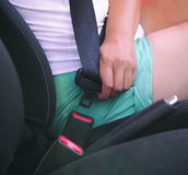 Woman buckles up the seat belt before driving car Royalty Free Stock Photography
