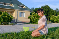 Woman with Bug Net Kneeling on Lawn Stock Photo
