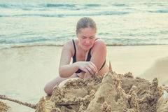 Woman build a castle of sand on the ocean. Royalty Free Stock Photography