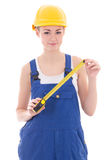 Woman builder in blue coveralls holding measure tape isolated on Stock Image