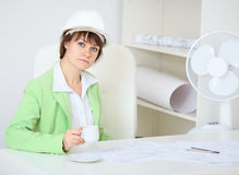Woman - a builder in helmet with cup in hand Royalty Free Stock Photography