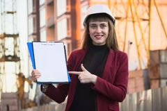 Woman builder holding blueprints, clipboard. Smiling architect girl in helmet at building background. Woman builder holding blueprints, and point to clipboard Stock Photography