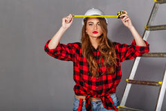 Woman builder holds tape measure Royalty Free Stock Photos