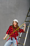 Woman builder holds tape measure Royalty Free Stock Images