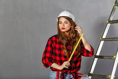 Woman builder holds tape measure Stock Photography