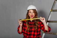 Woman builder holds tape measure Stock Photo