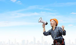 Woman builder with megaphone Stock Photo
