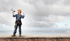 Woman builder with megaphone Royalty Free Stock Photo