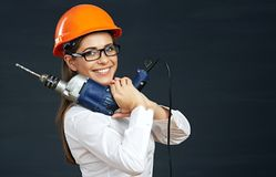 Woman builder portrait with drill. Smiling business woman against black background Stock Photos