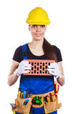 Woman builder in the uniform holds a brick Royalty Free Stock Photos