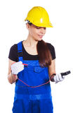 Woman builder in the uniform holds a multitester Stock Photography