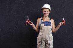 Woman builder worker in uniform holds wirecutter. Electrician female in helmet. Professional electric engineer. royalty free stock photos
