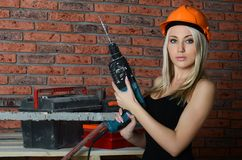 Woman in a building helmet with a drill in hands Stock Images