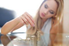 Woman building money column on desk Royalty Free Stock Image