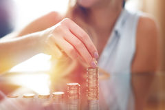 Woman building money column in sunset closeup Royalty Free Stock Photos