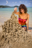 A woman building a sandcastle. On the beach Royalty Free Stock Image