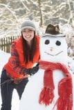 Woman Building Snowman In Garden stock photography