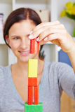 Woman building tower with building blocks royalty free stock images