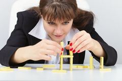 Woman building a tower on table with domino Stock Photos