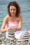 Woman builds stone stacks on pebble beach Royalty Free Stock Photo