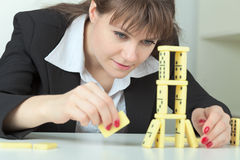 Woman builds tower of dominoes bones on table Stock Photography