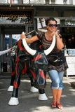 Woman and bull. ODESA, UKRAINE - 24 August 2009: Caucasian woman standing near plastic bull on street Royalty Free Stock Images
