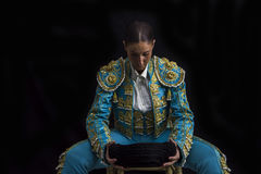 Woman bullfighter sitting on a chair looking at his montera Stock Image