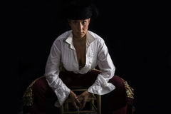 Woman bullfighter sitting on a wooden chair holding a rosary Stock Photo