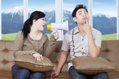 Woman with bullhorn screaming at man. Picture of Asian women looks angry and screaming at a men with a megaphone while sitting on the sofa at home Royalty Free Stock Images