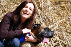 Woman with bullmastiff dog. Smiling young woman holding bullmastiff dog, haystack in background Royalty Free Stock Image