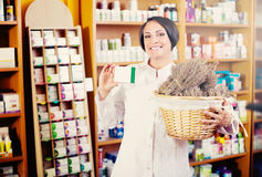 Woman with bunch of dried herbs in drugstore Stock Photography