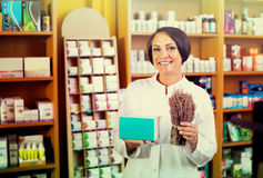 Woman with bunch of dried herbs in drugstore Royalty Free Stock Images